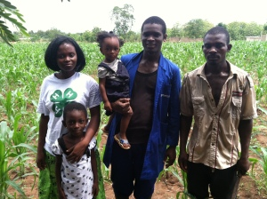 Welbeck (center) with his family on the corn fields that he farms through a community-based 4-H club outside of the city of Koforidua, Ghana. Photo by Kiera Butler.